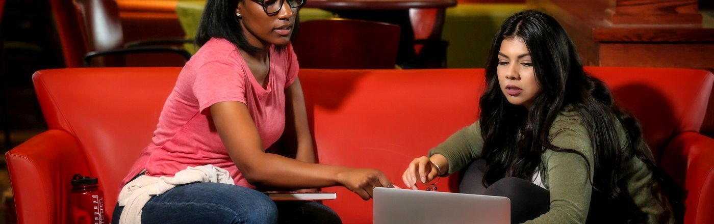 Students on red couch with laptop